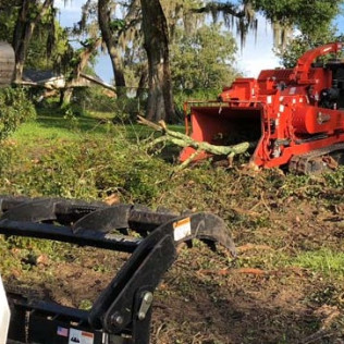 Several heavy duty machines performing land clearing services in Brandon, Florida