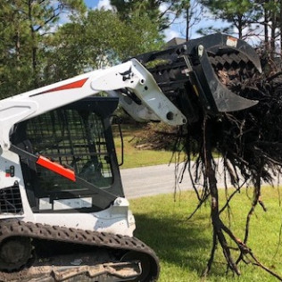 A small machine picking up a tree stump during tree stump removal services in Brandon, Florida